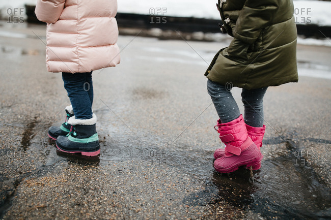 Two little girls splashing in melting snow puddles in the street