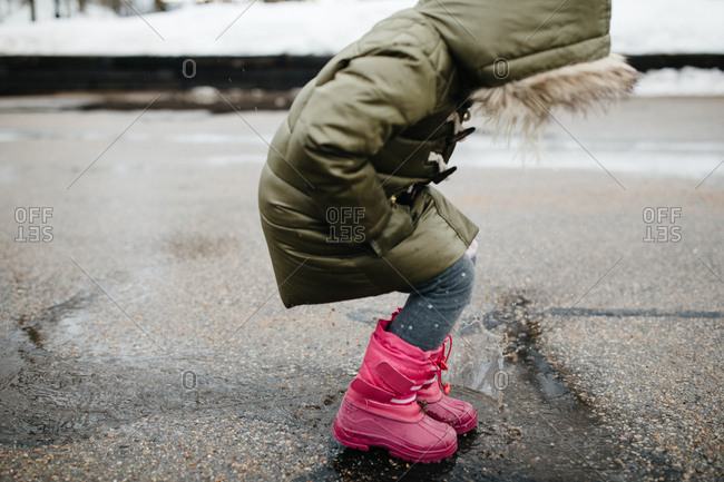 Young girl splashing in melting snow puddles in the street