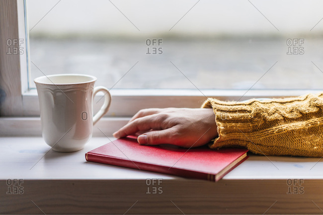 Crop person hand in yellow cozy warm sweater with book and cup of tea on windowsill near window in Faroe Islands