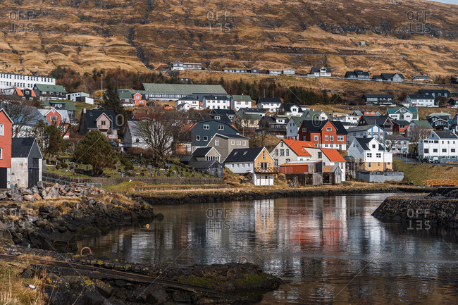 Lovely houses of small town located near small lake under a hill on sunny day on Faroe Islands