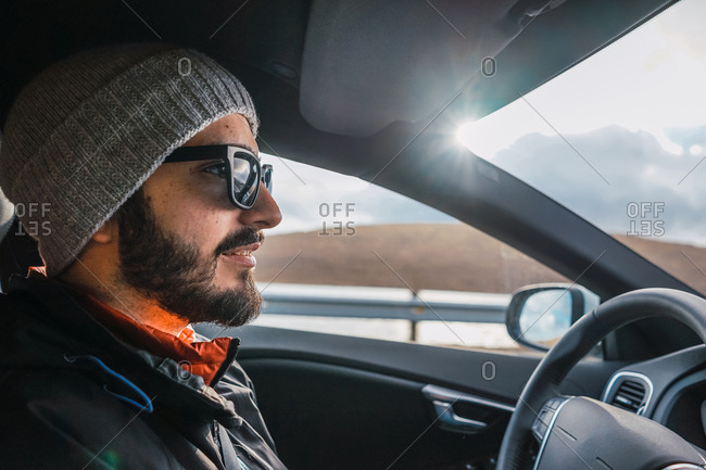 Side view of male driver in sunglasses riding car on countryside road during trip on Faroe Islands