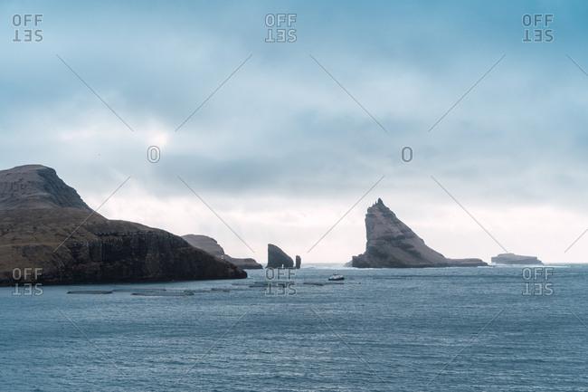 Landscape of calm sea water against gray clouds near Faroe Islands