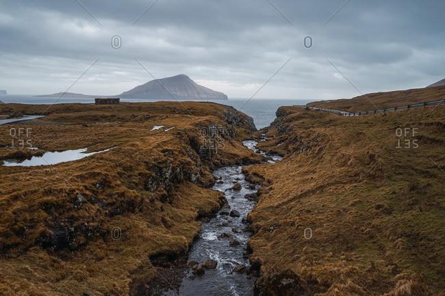 Curvy asphalt road going through hilly terrain on cloudy day on Faroe Islands