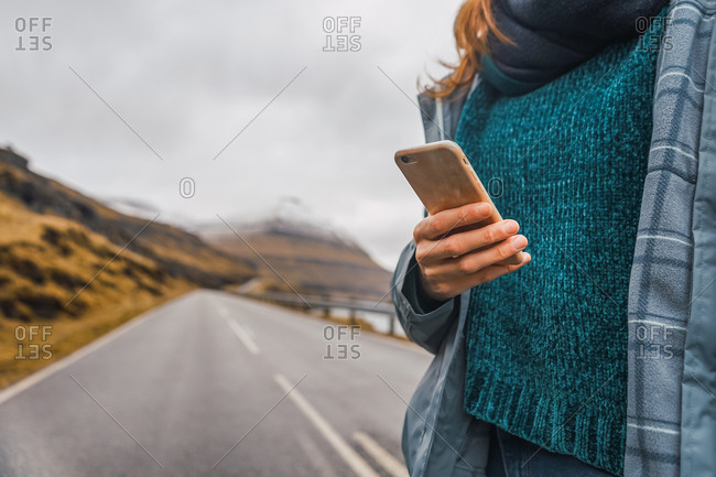 Crop unrecognizable female in warm clothes using mobile phone standing on asphalt road leading to mountains on Faroe Islands