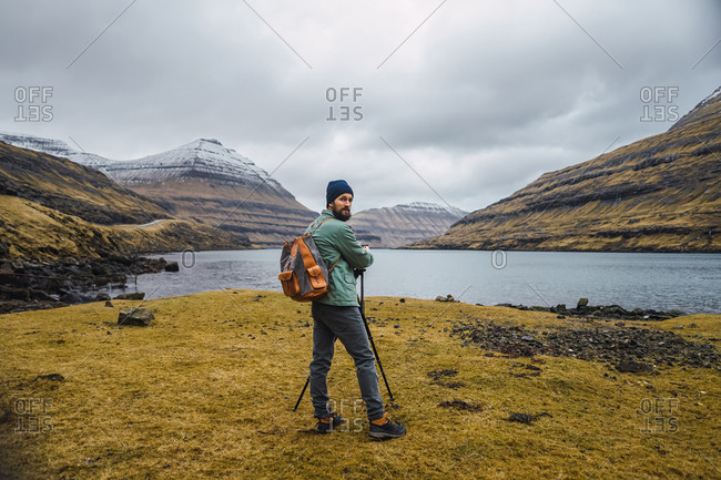 Back view of bearded man in winter clothes using a photo camera on a tripod outdoors in Faroe Islands landscape while looking at camera