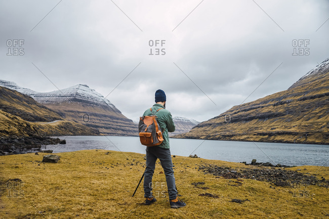 Back view of anonymous bearded man in winter clothes using a photo camera on a tripod outdoors in Faroe Islands landscape