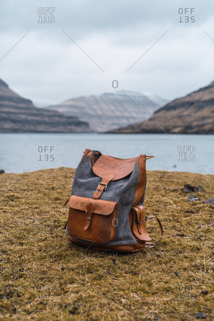 Women briefcase on shore with dry grass by lake in mountains on Faroe Islands