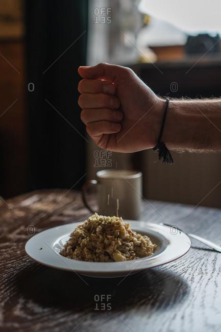 Crop male hand sprinkling porridge in plate on table on Faroe Islands