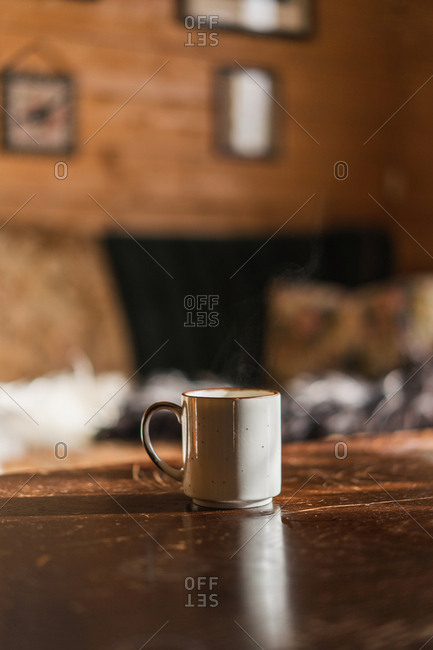 Mug of hot steamy beverage placed on wooden table in the morning indoors