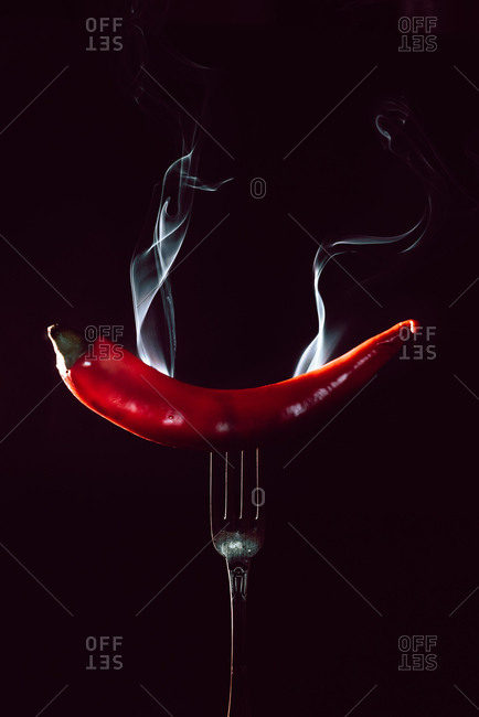 red chili pepper on fire in fork on a black background