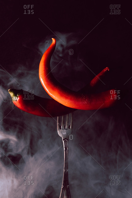 two red chili pepper in fork on a black background with smoke