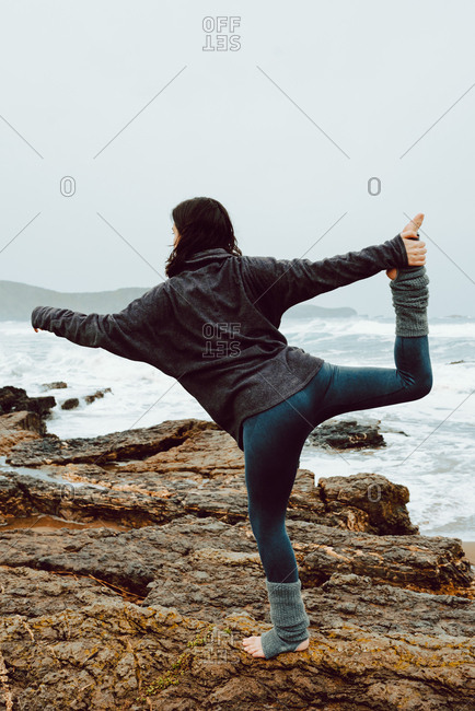 Young woman with upped hand and legs meditating and standing on rocks near sea