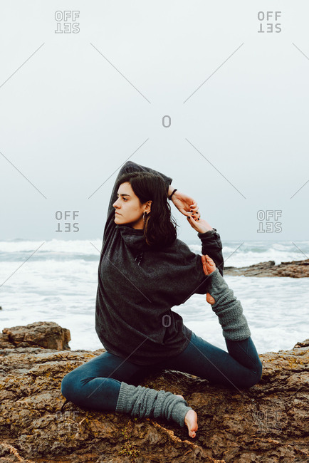 Young woman with upped hand and legs meditating and sitting on rocks near sea