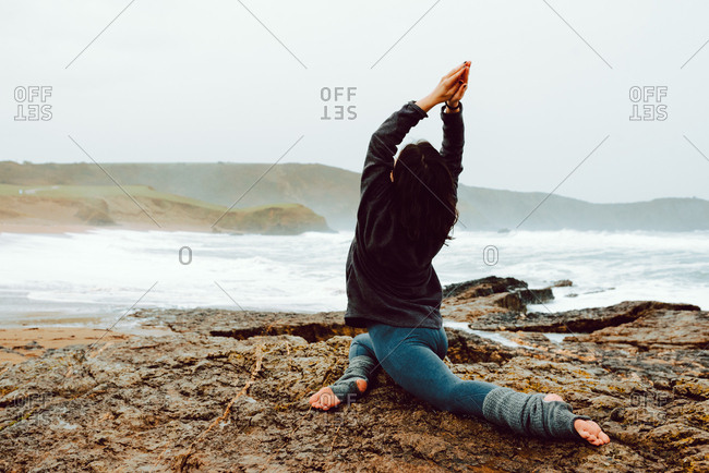 back view of young woman with upped hands and meditating and sitting on rocks near sea