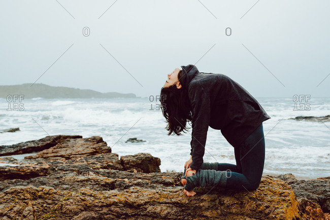 young woman with meditating practicing yoga and sitting on rocks near sea
