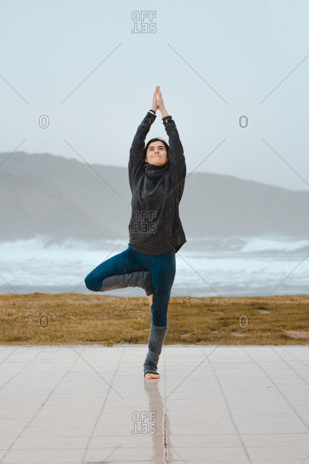 young woman practicing yoga while standing in a mountain landscape near sea