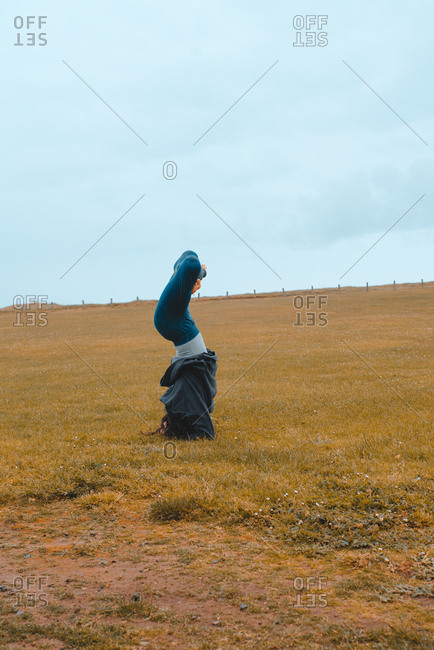 Pretty sporty woman standing upside down while relaxing and meditating on a field.