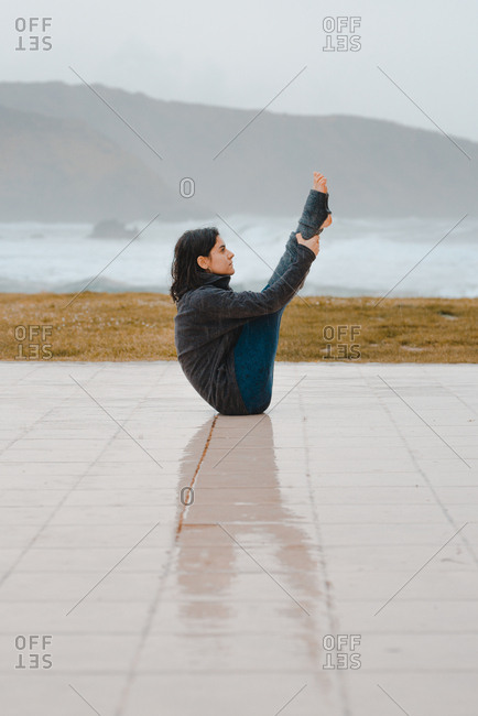 young woman practicing yoga while sitting in a mountain landscape near sea