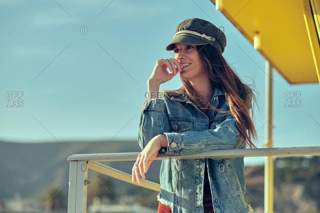 Pretty fashionable brunette woman in cap and jeans posing on balcony with railing and looking away on sunny day