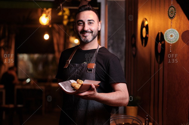 Positive bearded man in apron smiling while serving tasty snack in luxury restaurant
