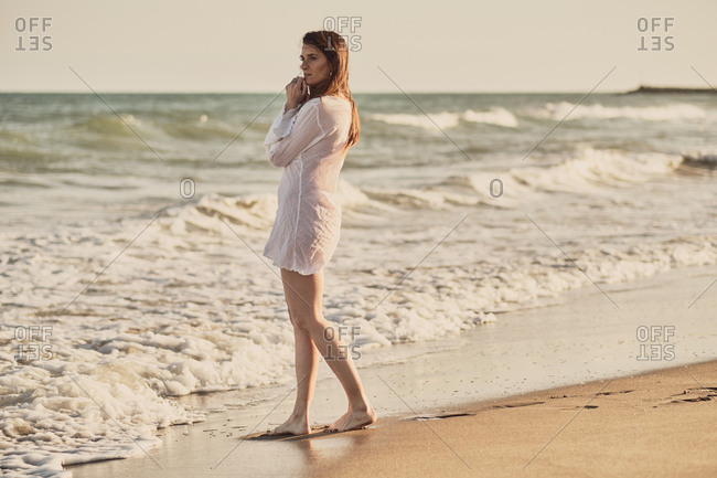 Happy brunette woman in the beach at golden hour with a white dress