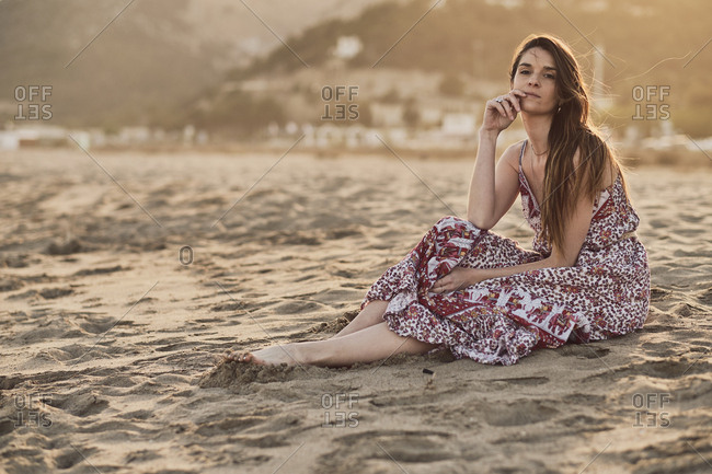 Happy brunette woman sitting in the beach at golden hour