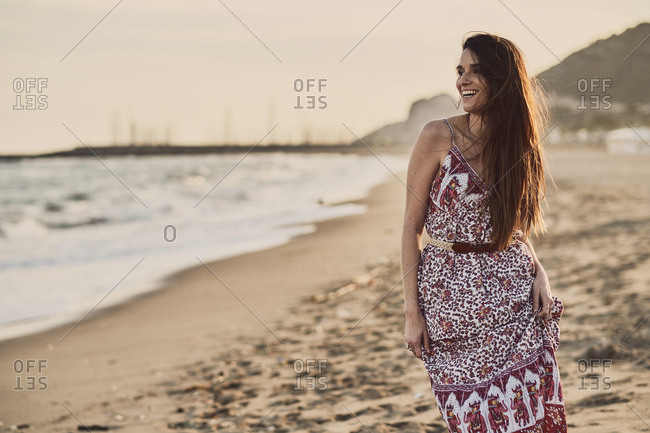 Happy brunette woman in summer dress in the beach at golden hour