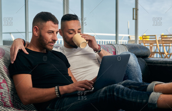 Handsome homosexual men smiling looking at laptop while relaxing on sofa drinking coffee and hugging at home