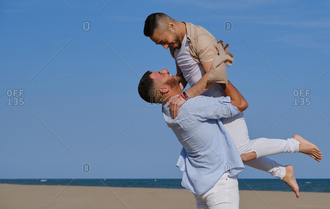 Side view of happy gay man lifting up and going to kiss boyfriend on deserted beach on summertime