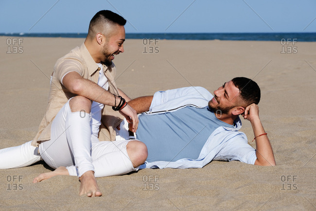 Handsome homosexual men touching and looking at each other while resting on beach in summer