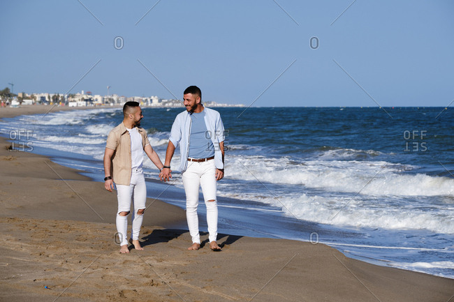 Handsome homosexual men holding hands and looking at each other while relaxing on seaside