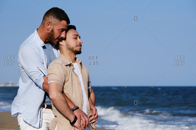 Side view of happy gay men standing on beach hugging, laughing and looking at sea