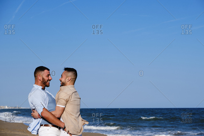 Side view of cheerful homosexual man lifting up happy boyfriend with outstretched arms on blue sky background
