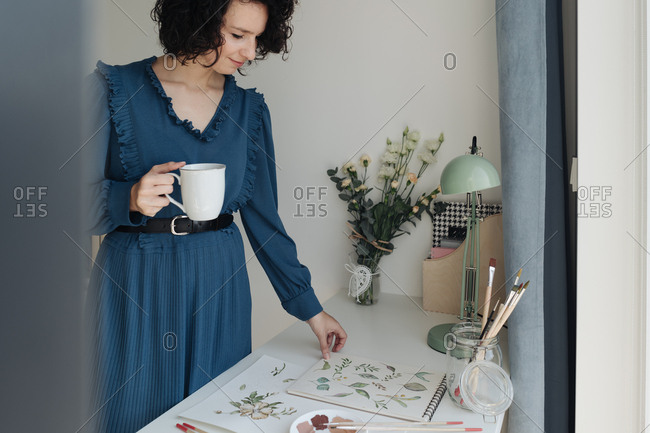 Brunette woman artist standing next to a table with cup of coffee and looking at drawings in workplace