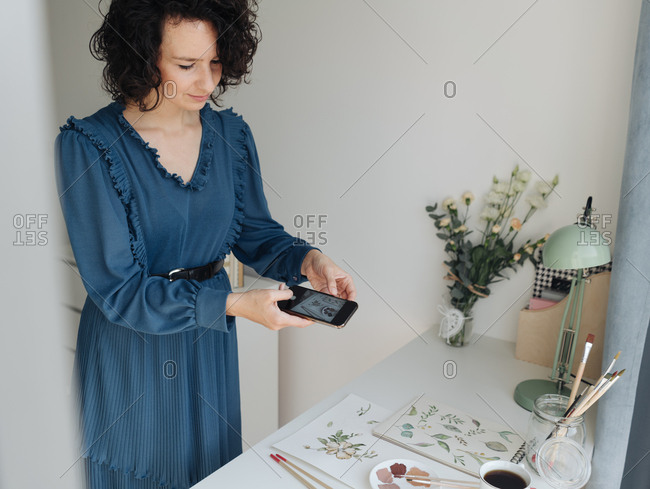 Woman artist in blue dress taking pictures on mobile phone of watercolor works on table in studio