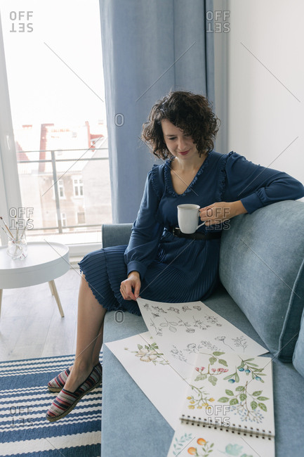 Beautiful young brunette female sitting on sofa and looking album with drawings at home while enjoying a cup of coffee