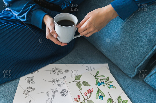 Crop view of anonymous woman artist sitting on sofa and looking album with drawings at home while enjoying a cup of coffee