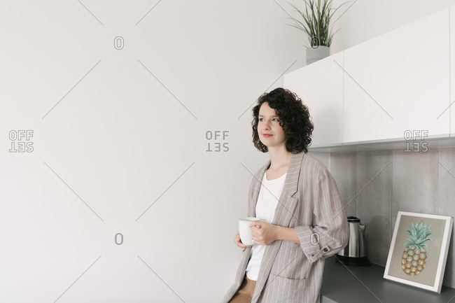 Elegant pensive woman in modern living room with a cup of coffee