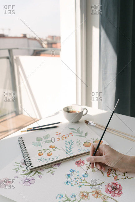 Crop person hand with brush painting watercolor flowers on large sheet at desk