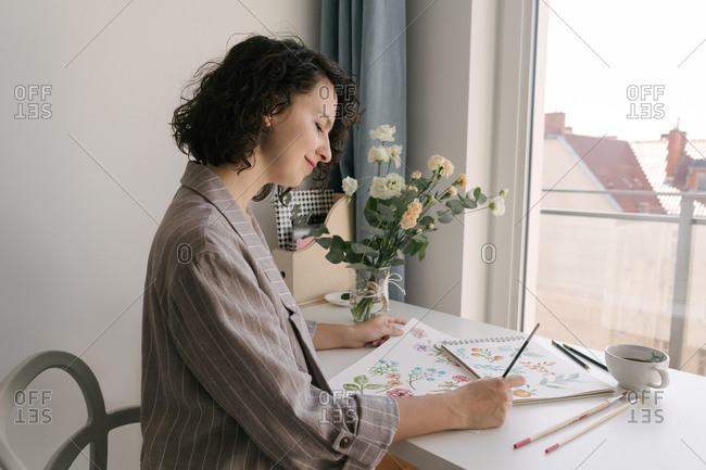 Elegant woman with brush painting watercolor flowers on large sheet at desk