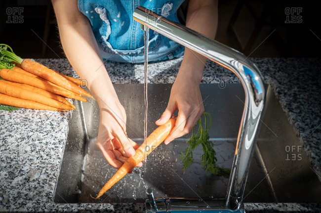 Hands of unrecognizable female washing ripe carrot under clean water over sink at home