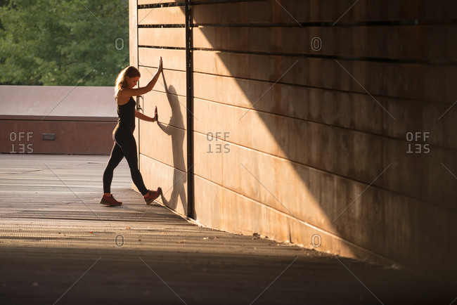 young woman stretching after running and leaning in a street wall