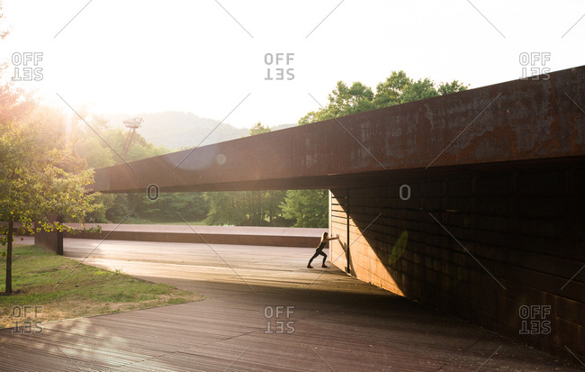 young woman stretching after running and leaning in a amazing geometrical building