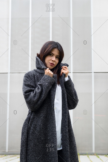 Stylish young woman looking at camera and wrapping in elegant warm coat while standing on city street