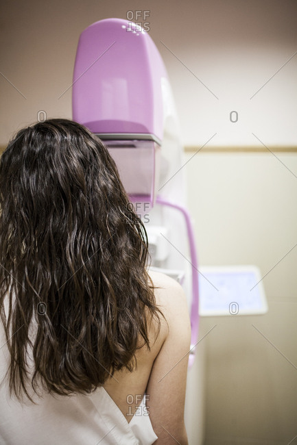 Female patient beside digital mammography unit