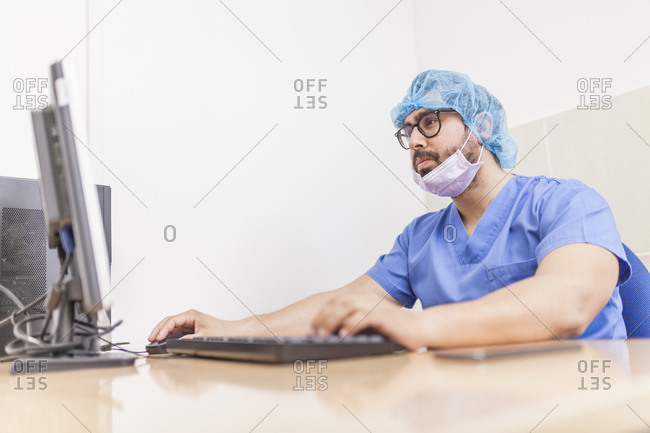 male surgeon using her computer in her office before the surgery