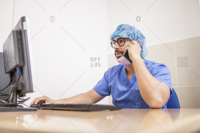 male surgeon using her computer and his smartphone in her office before the surgery