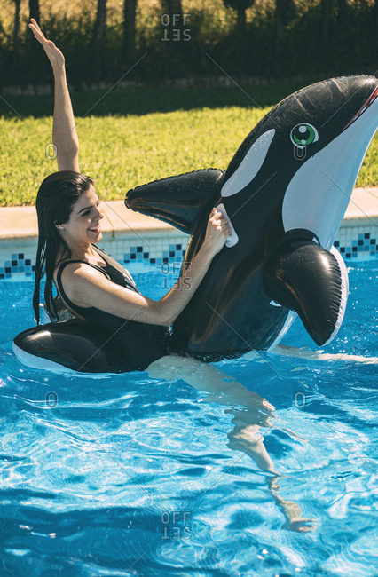 Excited young woman having fun in pool with inflatable fish toy in sunny day.