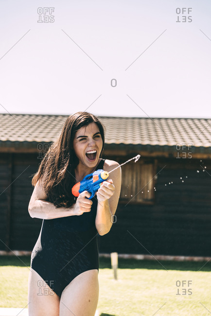 Woman aiming with water-pistol