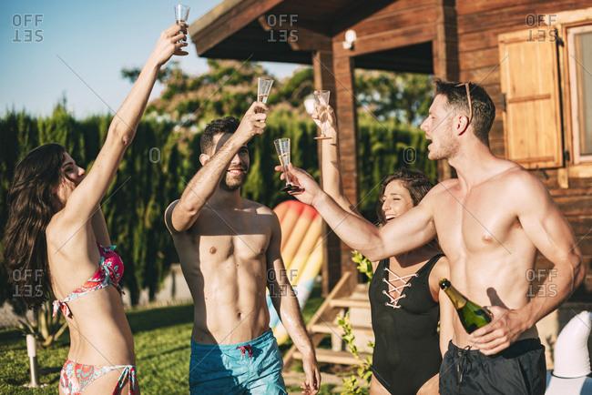 Friends drinking champagne in yard of summerhouse